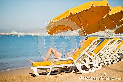 Girl relaxing on a beach chair near the sea