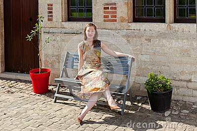 Girl relaxing on bench in front of antique house
