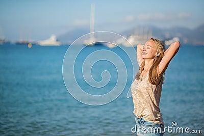 Girl relaxing near the sea, enjoying her vacation