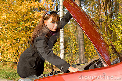 Girl repairs the car motor