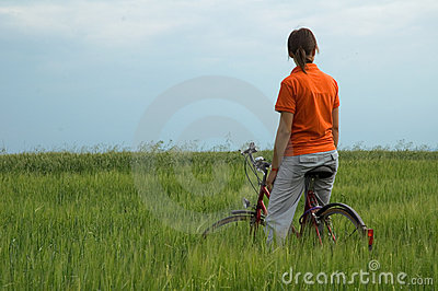 Girl resting on bicycle in green field