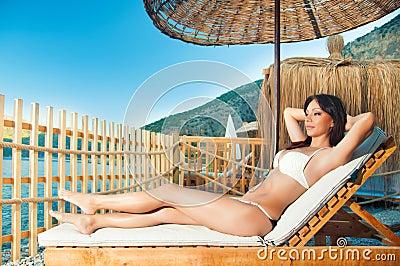 Girl resting on a sun lounger on the beach