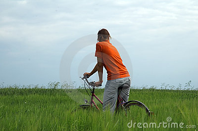 Girl riding bicycle in green field