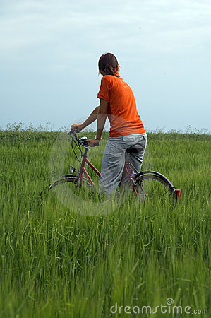 Girl riding bicycle in green field vertical