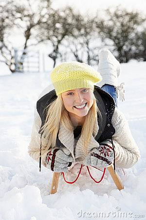 Girl Riding On Sledge In Snowy Landscape