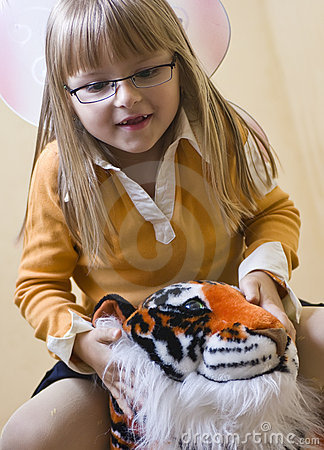Girl riding toy tiger