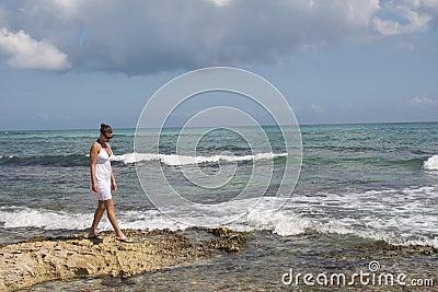 Girl on rocky shoreline