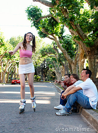 The girl on rollers under exulting of guys