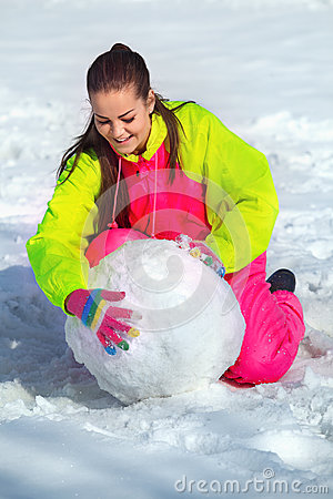 Girl rolling a huge snowbal