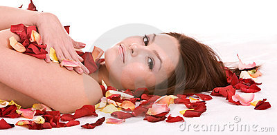 Girl in rose petal. Spa beautician.
