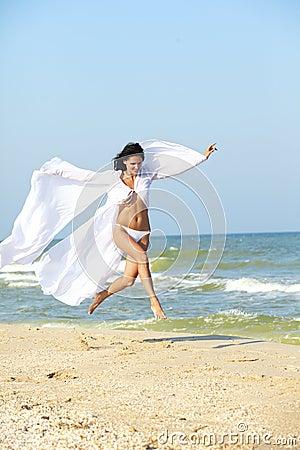 Girl run on coast of a sea