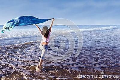 Girl running at beach with sarong