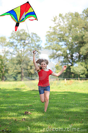 Girl running with a colorful kite outdoor smiling