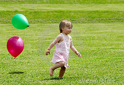 Girl running on a grass with balloons