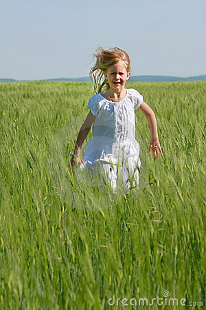 Girl running in green grass