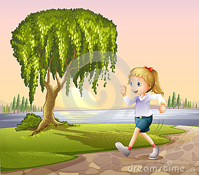 A girl running at the street with a giant tree