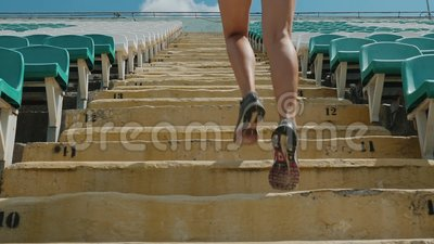 Girl running upstairs at a stadium. Close-up. Back view of a girl running upstairs at a stadium. Close-up legs. Slow motion shot. The camera follows the athlete stock footage