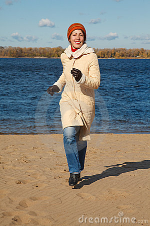Girl Runs Along Beach Autumn Day. Stock Images - Image: 13021944