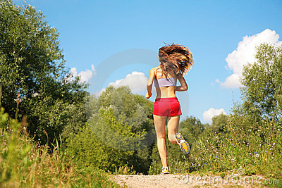 Girl runs in forest from back