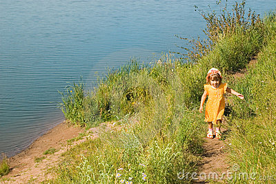 The girl runs on river bank