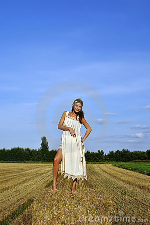 Girl in a rural clothing standing on the haystack