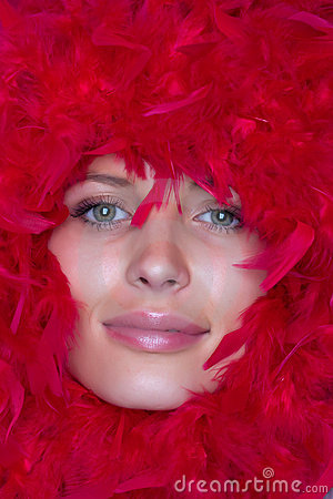 Girl s face in a frame of red feathers