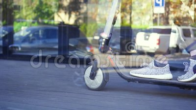 Girl`s feet on electric scooter close up,slow mo. Girl`s legs on electric scooter on road close up stock footage