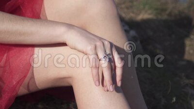 Girl`s hands with ring on fingers. Girl moves her hand resting on her leg and with a ring on her fingers stock video