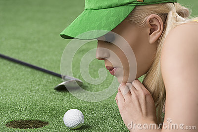 Girl s playing with golf ball, she blows on that