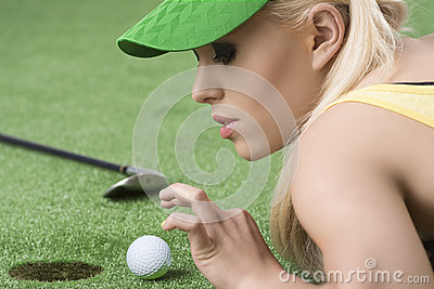 Girl s playing with golf ball, she looks the ball