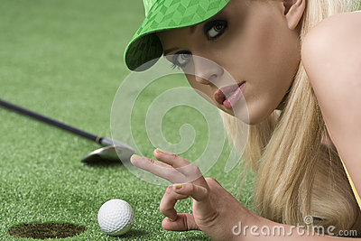 Girl s playing with golf ball looks in to the lens