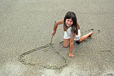 Girl in sand making hart
