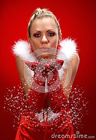 girl in santa cloth blowing snow