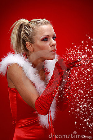 Girl in santa cloth blowing snow