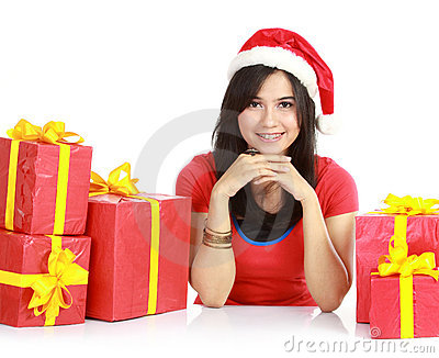 Girl in santa hat with pile of xmas gifts