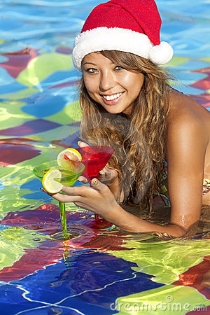 Girl in Santa hat sitting in the swimming pool