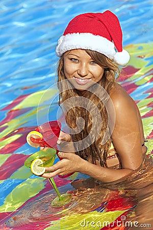 Girl in Santa hat sitting in the swimming pool