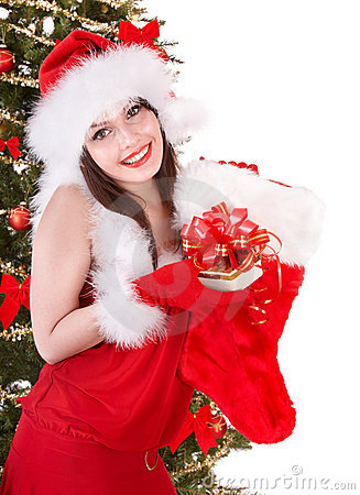 Girl in santa holding christmas sock and gift box.