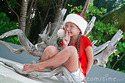Girl on Santa s hat making silence gesture