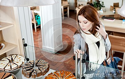 Girl in scarf looking at the bakery glass case