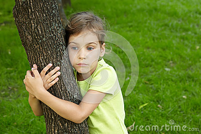 Girl with serious face stands, embracing tree