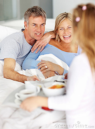 Girl serving breakfast to her parents to the bed