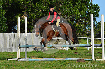 Girl show jumping with pony