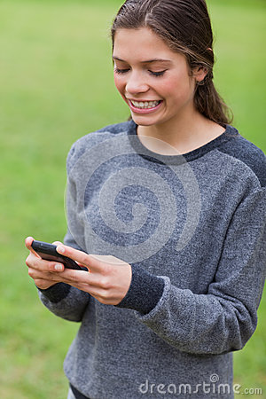 Girl showing a beaming smile while sending a text