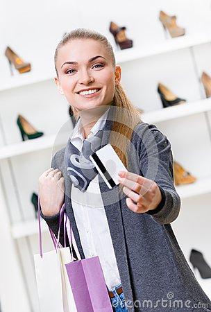 Girl showing credit card in footwear shop