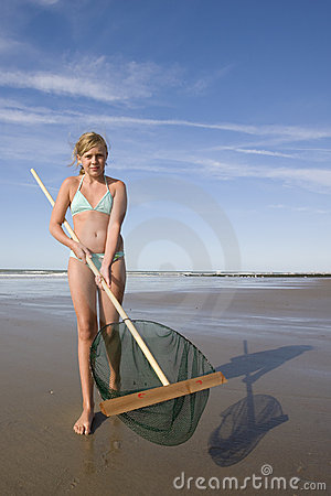 Girl showing her fishing net at the beach