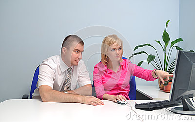 Girl shows something on the monitor to a colleague