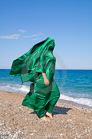 Girl silhouette in green tissue on the sea beach