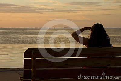 Girl in Silhouette Looking at Sunset