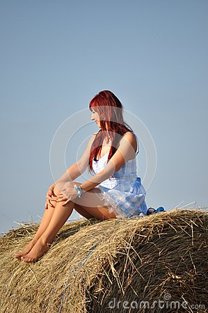 Girl sit on haystack